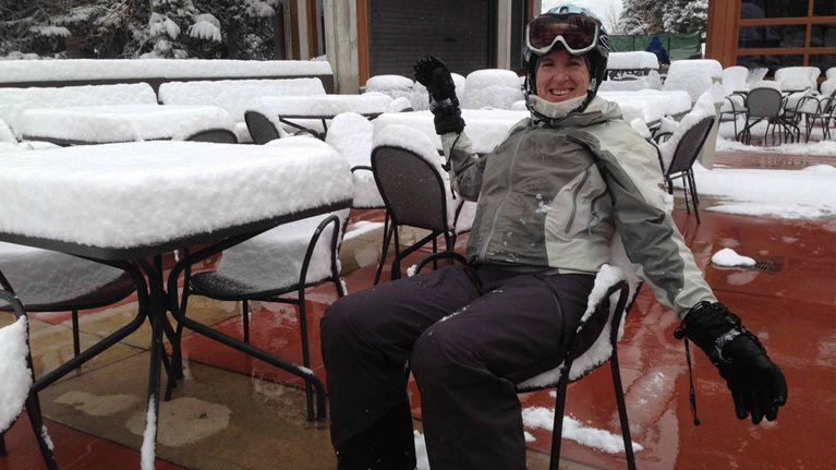 Diane Smith-Gander in ski gear sits in front of a table with several inches of snow on it